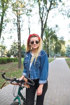 Ein lächelndes mädchen in der sonnenbrille und einer jeansjacke steht in einem parkrad, schaut in die kamera und lächelt.