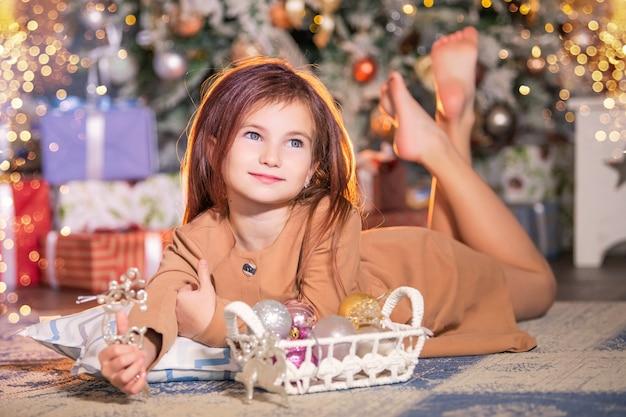 Ein lächelndes mädchen liegt auf dem boden vor dem hintergrund eines weihnachtsbaumes und hält eine weihnachtsdekoration in form eines hirsches.