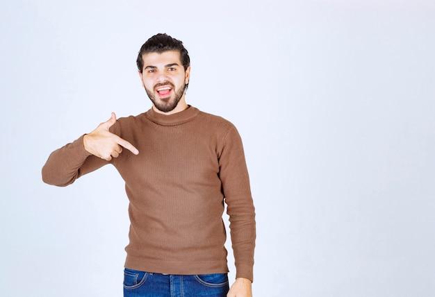 Ein lächelndes modell des jungen mannes, das auf sich selbst steht und zeigt. foto in hoher qualität