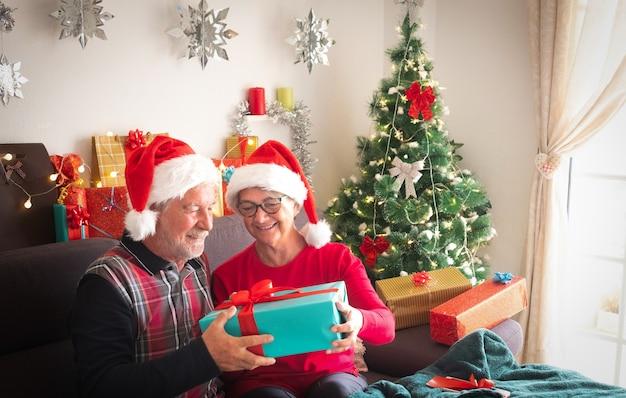 Ein lächelndes paar von mann und frau in weihnachtsmützen mit vielen geschenken für sie und für die familie. weihnachtsbaum im hintergrund