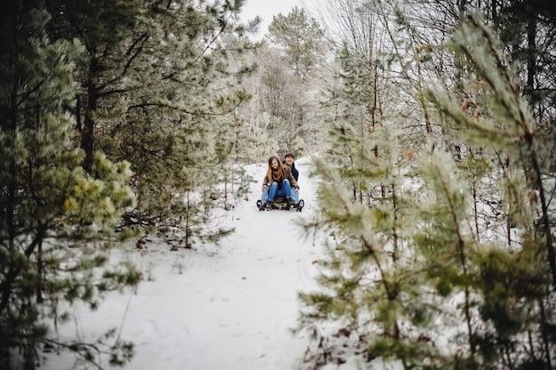 Ein lächelndes und glückliches paar genießt es, in einem wald oder stadtpark bergab zu rodeln. zwei junge leute, die auf einem holzschlitten am schneewintertag gleiten.