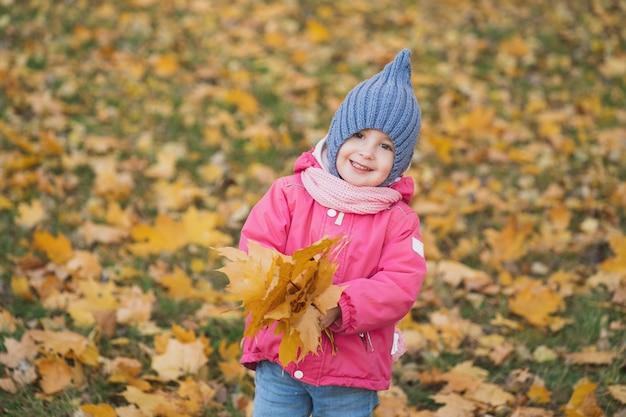 Ein lächelndes und offenes kind spielt mit herbstlaub, das mädchen geht im park spazieren und freut sich das kind...
