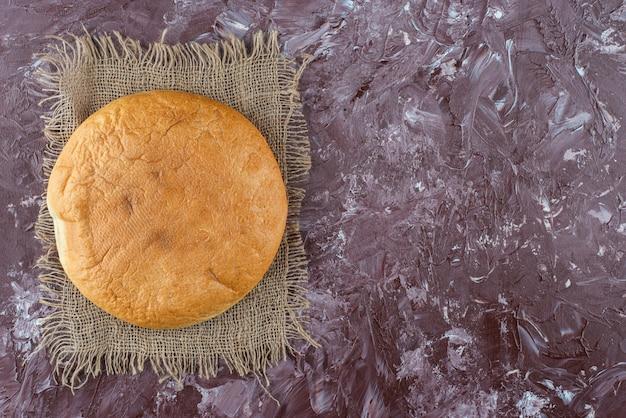 Ein laib rundes brot mit einer kruste auf einem sack.
