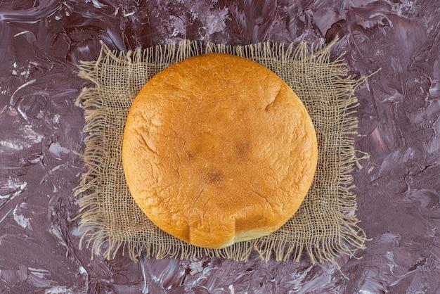 Ein laib rundes brot mit einer kruste auf einem sack