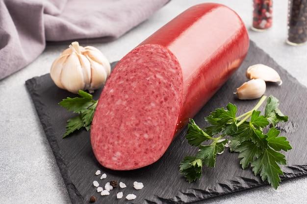 Ein laib salami servelatwurst auf einem schneidebrett mit petersilie und gewürzen und knoblauch.