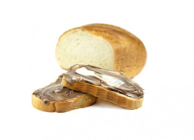 Ein laib weißbrot, in scheiben geschnitten und mit schokoladenpaste bestrichen
