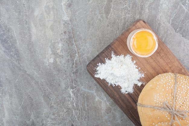 Ein laib weißbrot mit eigelb und mehl auf holzbrett