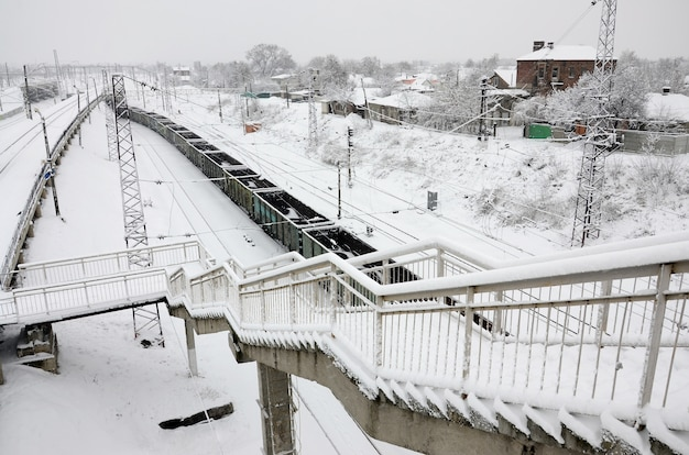 Ein langer güterwagenzug bewegt sich entlang der bahnstrecke. bahnlandschaft im winter nach schneefall