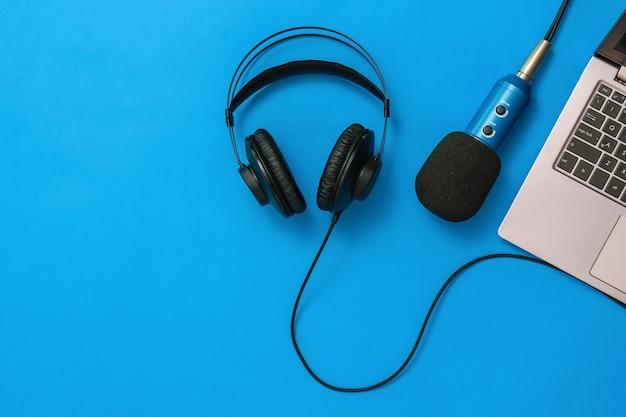 Ein laptop mit angeschlossenem mikrofon und kopfhörern auf blauem grund. das konzept der arbeitsplatzorganisation. geräte zum aufnehmen, kommunizieren und musikhören. flach liegen.
