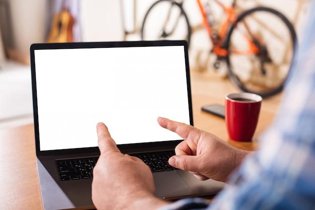 Ein laptop mit einem leeren weißen bildschirm auf dem hintergrund einer häuslichen umgebung.
