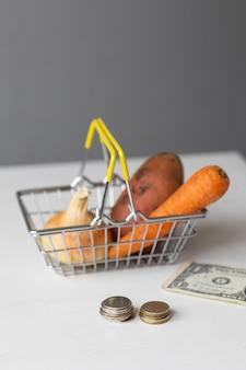 Ein lebensmittelkorb aus metall im supermarkt mit gemüse und papiergeld und münzen auf einem weißen tisch