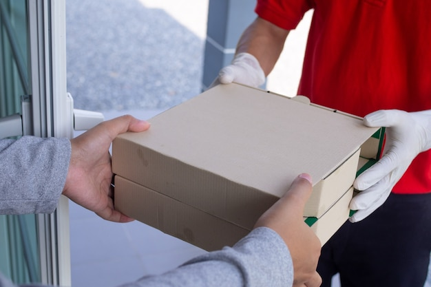 Ein lebensmittellieferant, der eine rote uniform und hygienehandschuhe trägt und einem kunden eine lebensmittelbox liefert, ruft online an, um zu hause zu essen. online-lieferkonzepte.