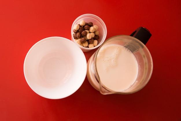 Ein leckeres und gesundes frühstück, gesundes essen, werbung für schokoladenbällchen mit milch. leere platte, säuglingsnahrung und milch auf rot