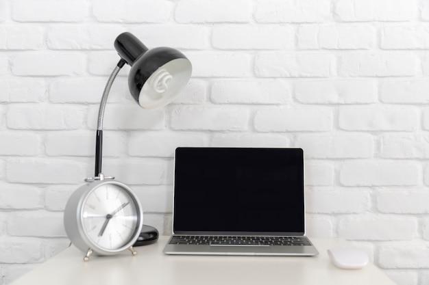 Ein leerer bildschirm laptop-computer auf weißem schreibtisch mit lampe und weißer backsteinmauer.