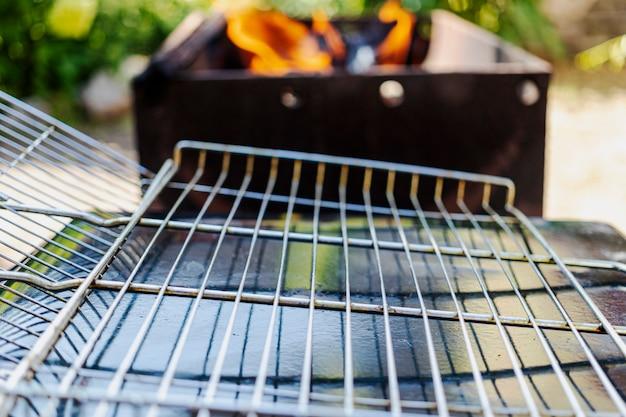 Ein leerer grillrost auf dem hintergrund eines grills, der zum auskleiden von fleisch oder gemüse darauf vorbereitet ist. ruhe in der natur.