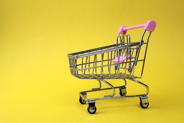 Ein leerer miniatur-supermarktwagen aus eisen steht auf einer leuchtend gelben wand mit platz für text. handels- und geschäftsthema.