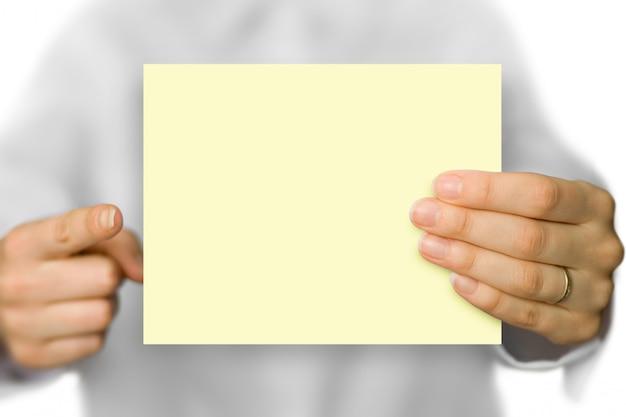 Ein leerer papierhintergrund, den eine hand hält und die andere hand mit einem finger zeigt