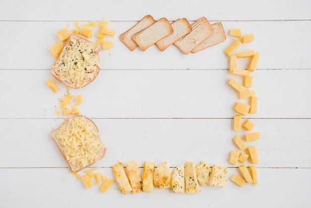 Ein leerer rahmen gemacht mit käse und brot auf weißem schreibtisch