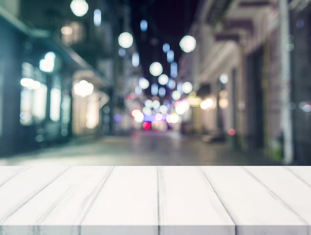Ein leerer schreibtisch vor unschärfe beleuchtete einkaufszentrum