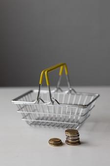 Ein leerer supermarkt-lebensmittelkorb aus metall mit münzen auf einem weißen tisch mit papiergeld