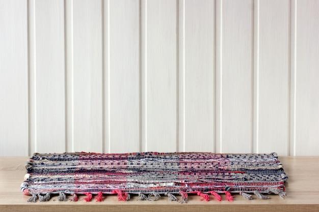 Ein leerer tisch mit einem rustikalen bunten teppich vor einer weißen holzwand im hintergrund, platz für ihr objektmodell