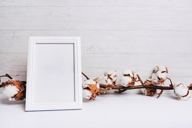 Ein leerer weißer rahmen vor baumwollblumenstamm auf schreibtisch gegen hölzernen hintergrund