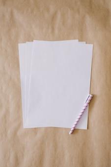 Ein leeres blatt a4-papier und ein stift liegen auf einem in handarbeit gemachten hintergrund und kopieren raum