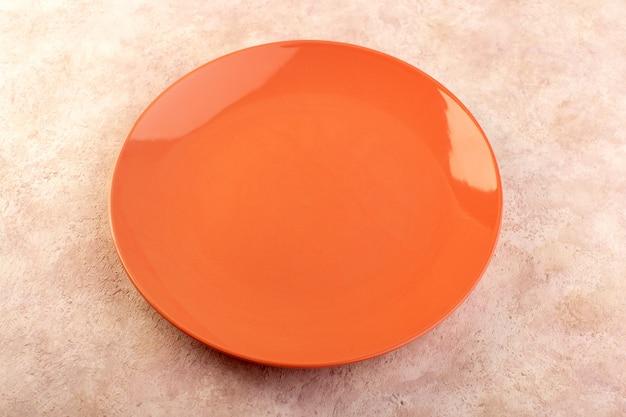 Ein leeres glas der orange runden platte der draufsicht machte isolierte mahlzeittischfarbe