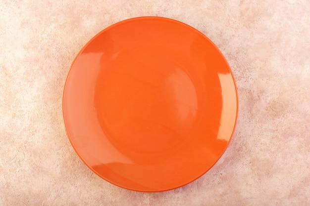 Ein leeres glas der orange runden platte der draufsicht machte isolierten mahlzeitentisch