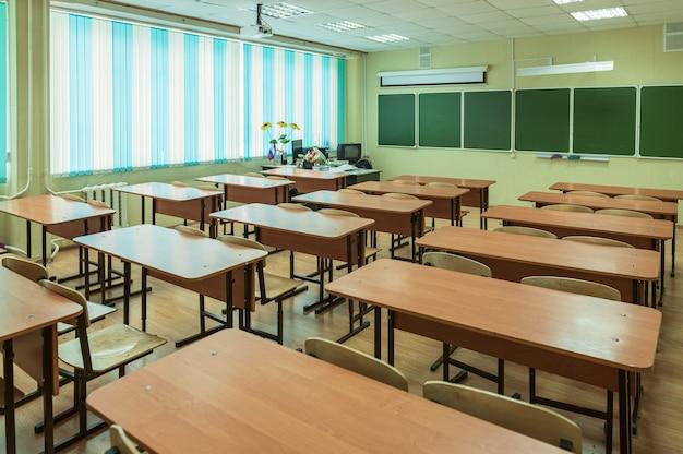 Ein leeres klassenzimmer in einer schule ohne menschen mit einem blumenstrauß auf dem lehrerpult