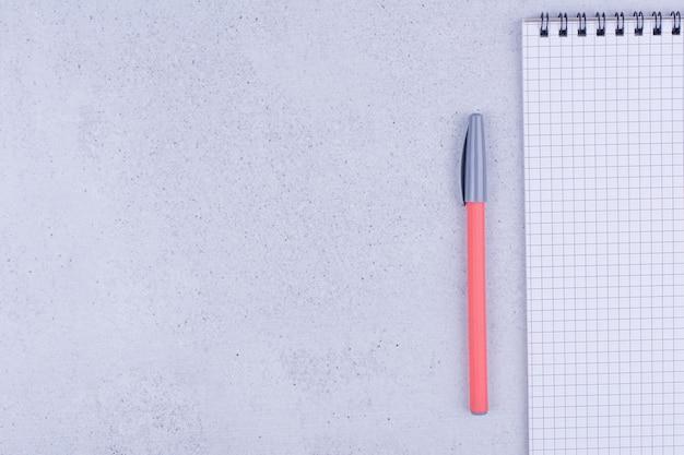 Ein leeres notizbuch mit farbstiften auf grauer oberfläche
