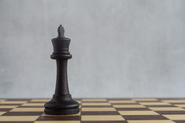 Ein leeres schachbrett und ein einzelner schwarzer könig darauf