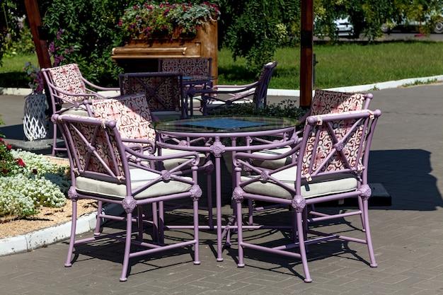 Ein leeres straßencafé mit bequemen stühlen unter vordächern im zentrum der stadt an einem sommer