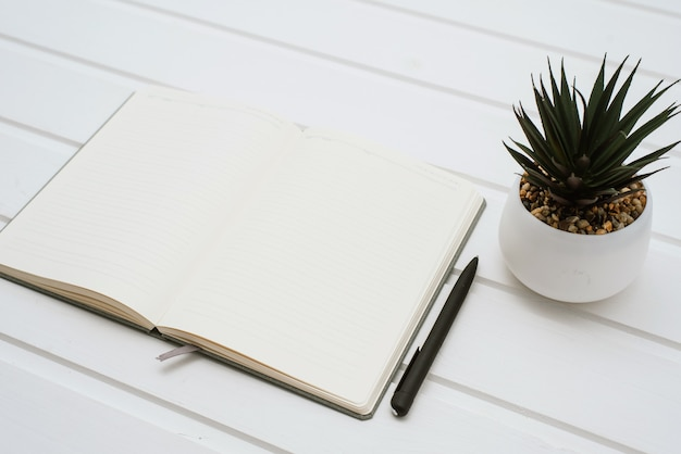 Ein leeres weißes notizbuch auf einem weißen hölzernen hintergrund neben einer hausblume in einem topf.