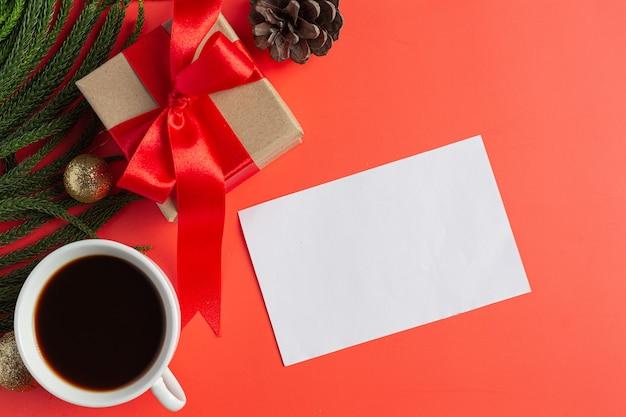 Ein leeres weißes papier, eine tasse kaffee und eine geschenkbox auf rotem boden