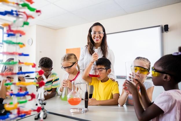 Ein lehrer, der mit den schülern tut wissenschaft aufwirft