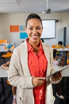 Ein lehrer, der mit tabletten-pc im klassenzimmer steht