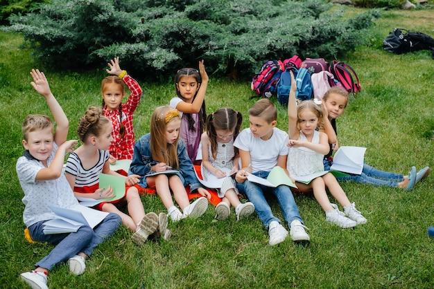 Ein lehrer unterrichtet eine klasse von kindern in einem park im freien. zurück in die schule, lernen während der pandemie.