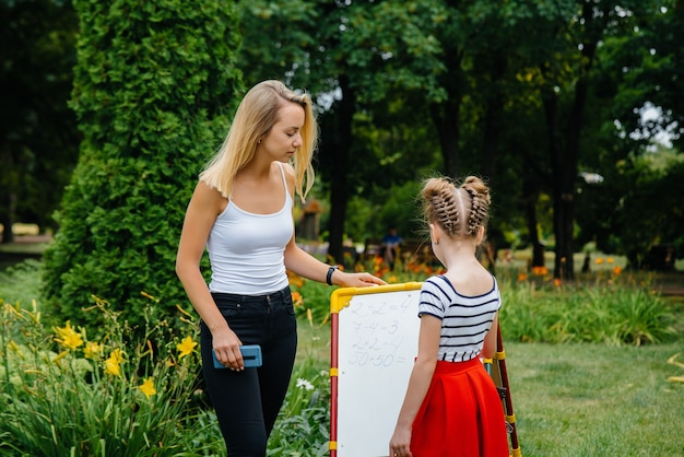 Ein lehrer unterrichtet eine klasse von kindern in einem park im freien. zurück zur schule, lernen während der pandemie.