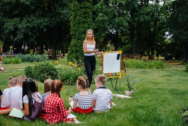 Ein lehrer unterrichtet eine klasse von kindern in einem park im freien