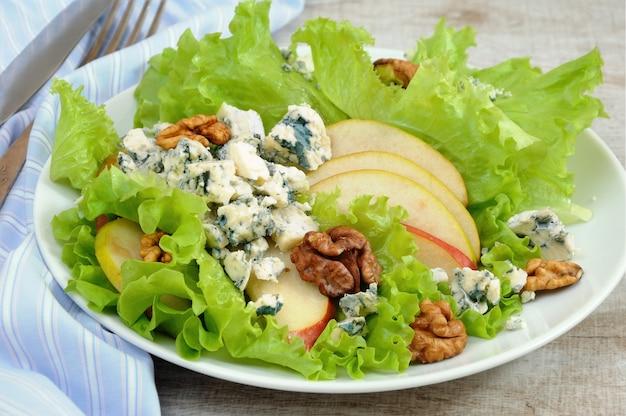Ein leichter salat mit birnenscheiben, gorgonzolastücken und walnuss, gewürzt mit olivenöl
