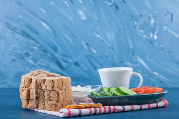 Ein leichtes frühstück, eine tasse tee, eine schüssel gurkenscheiben, tomaten und brot auf einem geschirrtuch auf dem blauen tisch.