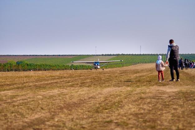 Ein leichtflugzeug landet auf einem feld in der nähe eines weinbergs. sonniger sommertag, leute beobachten und pflanzen.