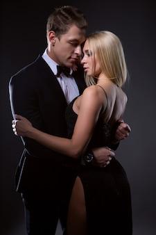 Ein leidenschaftliches paar, eine frau mit heller frisur im schwarzen abendkleid und ein gutaussehender mann im anzug mit fliege in einer zärtlichen umarmung