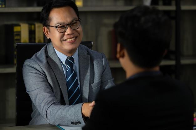 Ein leitender geschäftsmann in einer luxus-suite, der einem anderen mit einem smiley und aufrichtig und erfolgreich die hand schüttelt.