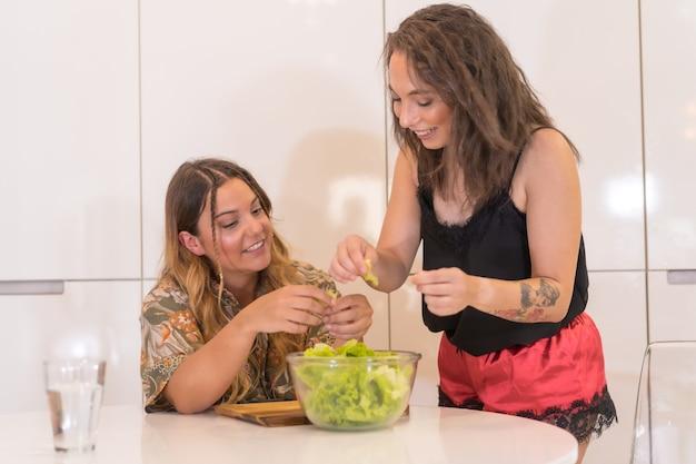 Ein lgbt-paar, das einen salat in der küche zubereitet, ein lesbisches mädchenpaar zu hause, ein mädchenbeziehungslebensstil