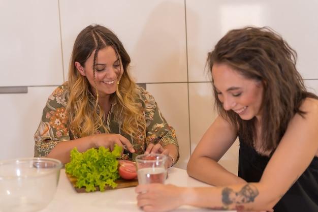 Ein lgbt-paar, das zu hause einen salat in der küche zubereitet, lesbisches mädchenpaar, mädchenbeziehungslebensstil