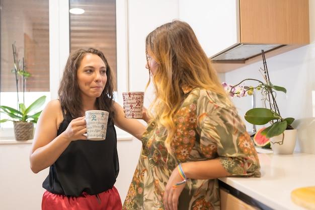 Ein lgbt-paar, das zu hause in der küche frühstückscafé isst, lesbisches mädchenpaar, mädchenbeziehungslebensstil