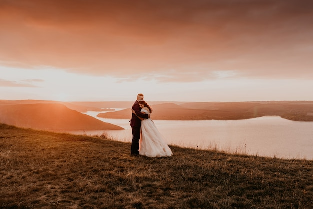 Ein liebendes paar, das jungvermählten heiratet, geht im sommer im herbst auf berg auf klippe über dem fluss spazieren