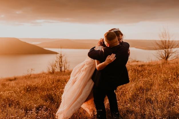 Ein liebendes paar, das jungvermählten in einem weißen kleid und einem anzugspaziergang heiratet, lächelt glücklich auf hohem gras im sommerfeld auf dem berg über dem fluss